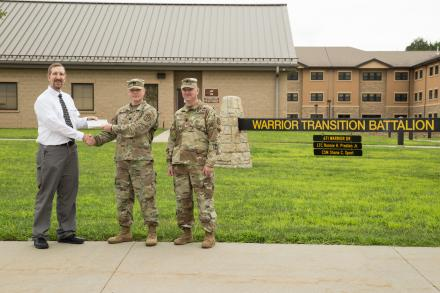 Kurt Teal, Dean of Fort Riley Academics, Technical Education and Military Outreach Programs at Barton Community College, presents a check for $3,250 to Bravo Company Commander Daniel Sheninger and Command Sergeant Major Shane Sport.